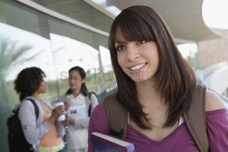 Pupil : Female student holding book at school smiling
