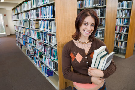 Learning : Female student holding books in library