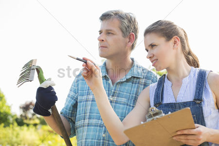Supervisor : Female supervisor explaining something to gardener at plant nursery