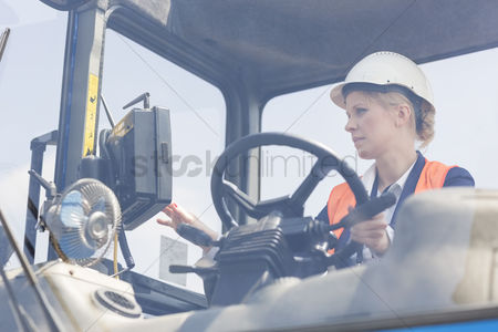 Forklift : Female worker operating forklift truck in shipping yard