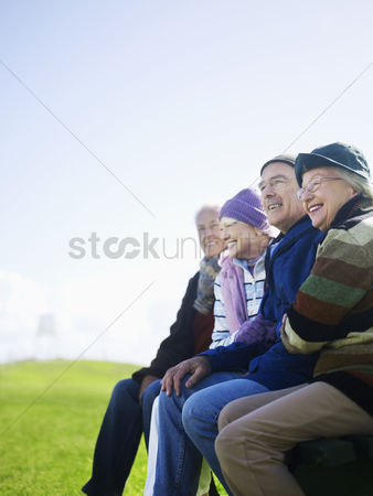 Women group outside : Four senior friends sitting outdoors laughing