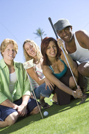 Women group outside : Four young friends on golf course portrait