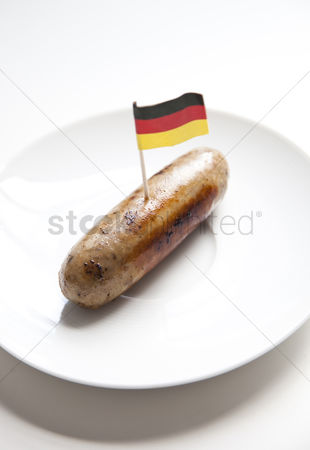 Sausage : Fried sausage in plate with german flag decoration against white background