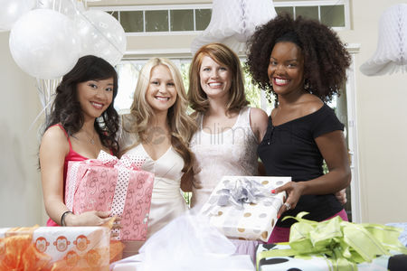 Celebrating : Friends standing together with gifts at bridal shower