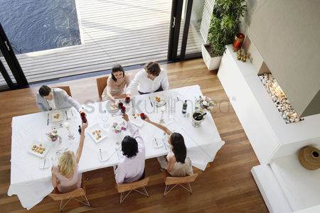 Interior : Friends toasting across table at a formal dinner party high angle view