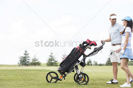 Pushing : Friends with equipment talking while walking at golf course against clear sky