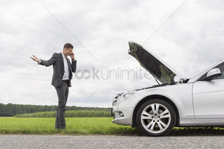 Land : Frustrated young businessman using cell phone by broken-down car at countryside