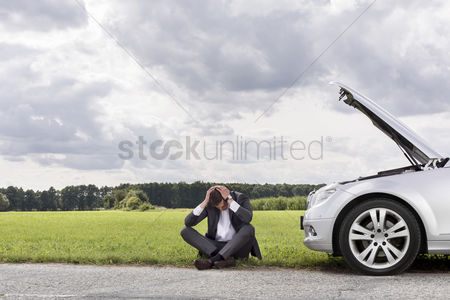 Land : Full length of businessman with hands on head sitting by broken down car at countryside