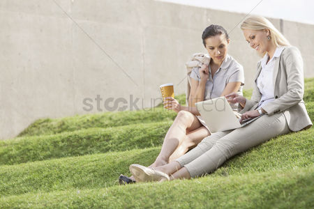 Steps : Full length of businesswomen with disposable coffee cup looking at laptop while sitting on grass steps