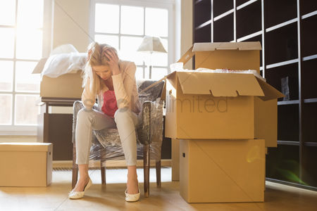 Pensive : Full-length of frustrated woman sitting by cardboard boxes in new house