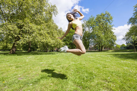 Grass : Full length of happy fit woman jumping in park