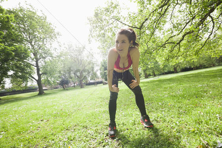 Fitness : Full length of tired fit woman taking break while exercising in park