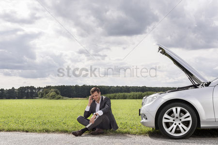 Land : Full length of unhappy young businessman using cell phone by broken down car at countryside