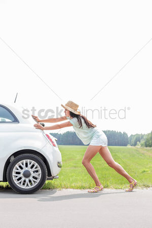 Pushing : Full-length of woman pushing broken down car on country road