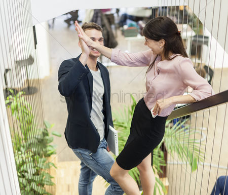 Girlfriend : Full length of young business couple doing high-five on staircase