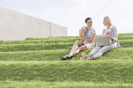 Steps : Full length of young businesswomen with disposable coffee cup and laptop sitting on grass steps against sky