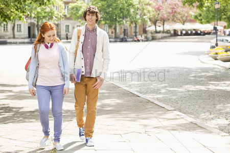 College : Full length of young male and female college students walking on footpath