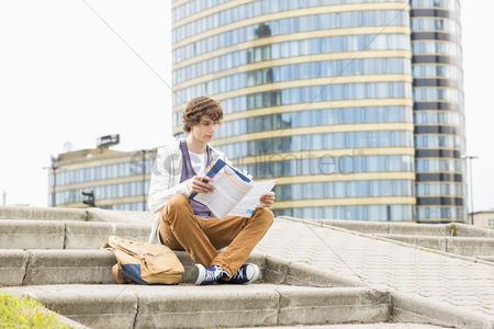 Steps : Full length of young male college student reading book against building