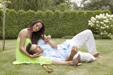 Sitting on lap : Full length of young man lying on woman s lap in park