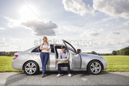 Land : Full length of young woman looking away while man reading map in car at countryside