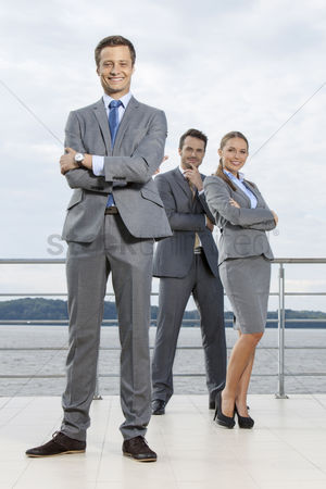 Leadership : Full length portrait of confident businessman standing with coworkers on terrace against sky