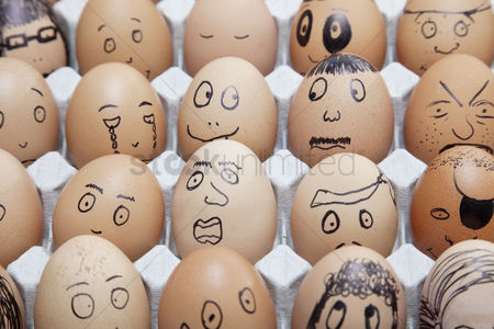 Creativity : Funny faces on painted on brown eggs arranged in carton