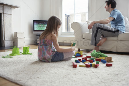 Match : Girl  5-6  sitting on floor playing with blocks father watching television