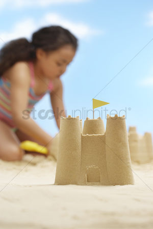 Flag : Girl  7-9 years  building sand castles on beach focus on sand castle in foreground