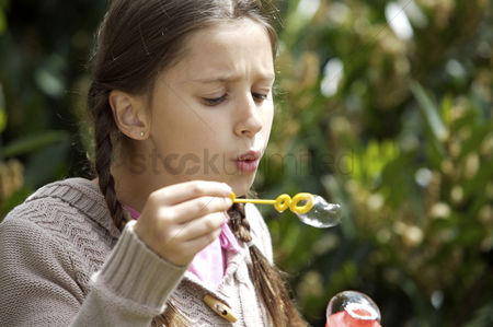 Blowing : Girl blowing bubbles with wand