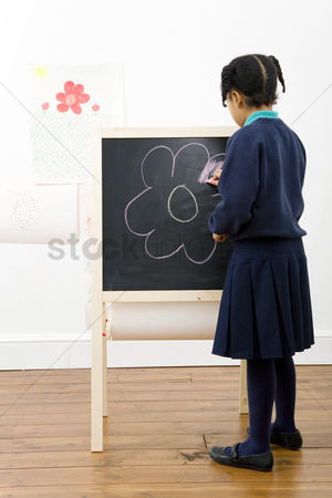 Pupil : Girl colouring a drawing on chalkboard