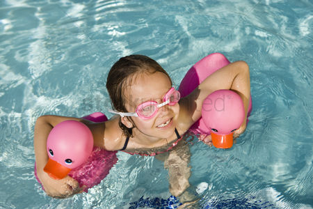 Children : Girl floating using two pink rubber ducks