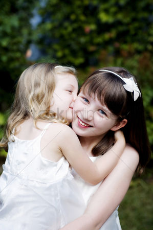 Kissing : Girl giving her sister a peck on the cheek