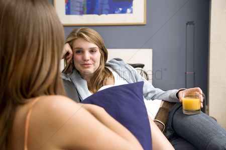 Teenager : Girl holding a glass of orange juice while talking to another girl