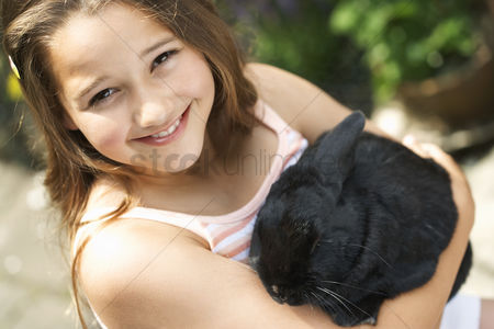 Domesticated animal : Girl holding rabbit