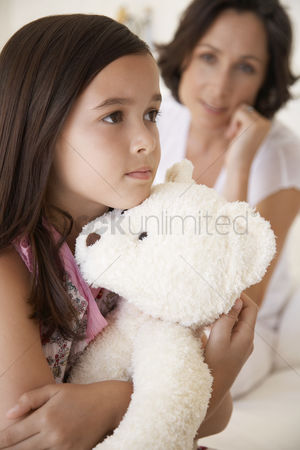 Moody : Girl hugging teddy bear half length mother in background
