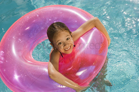 Posed : Girl inside pink float tube in pool