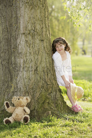 Gladness : Girl leaning against tree  holding straw hat