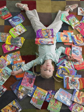 Obsessive : Girl lying on library floor with books scattered around view from above