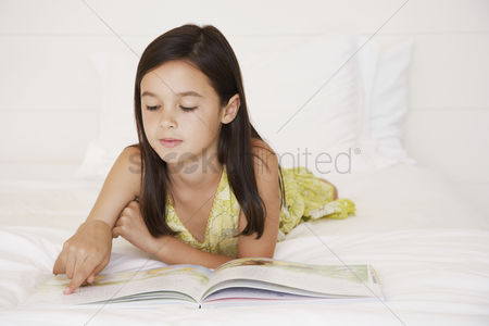 Careful : Girl reading story book lying on bed