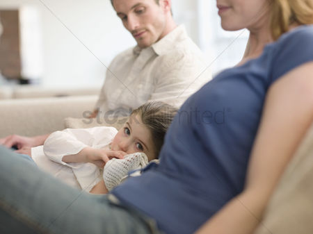Gaze : Girl resting on sofa between parents