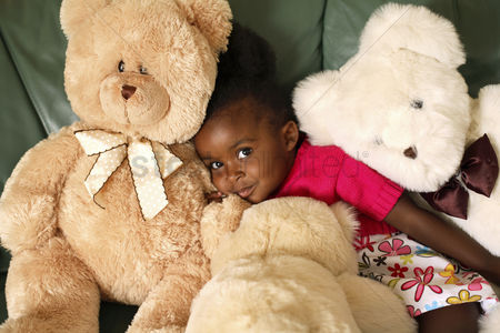 Comfort : Girl sitting on the couch with teddy bears