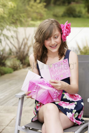 Birthday present : Girl smiling while reading her birthday card