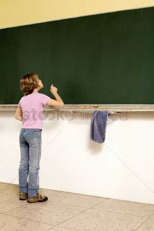 Wondering : Girl standing in front of blackboard holding a chalk