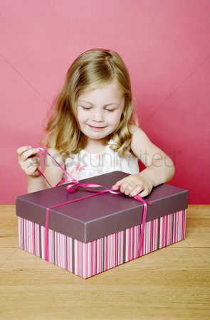 Celebrating : Girl unwrapping her present