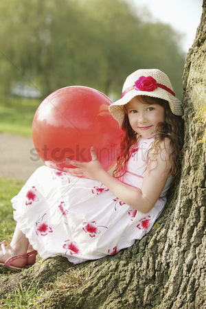 Gladness : Girl with red ball  leaning against tree