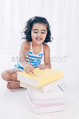 Bliss : Girl writing on a book with a pencil