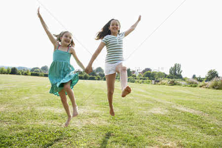 Cheerful : Girls running and jumping hand in hand through field