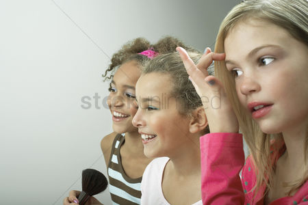 Maturity : Girls standing side by side putting on make-up fixing hair