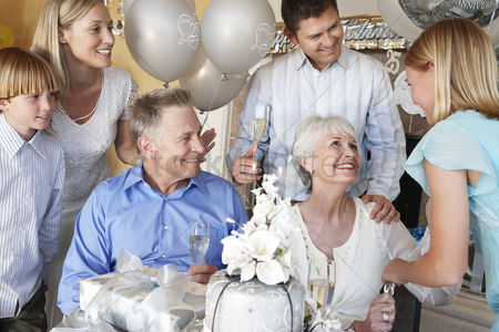 Celebrating : Grandmother smiling at granddaughter at party with whole family