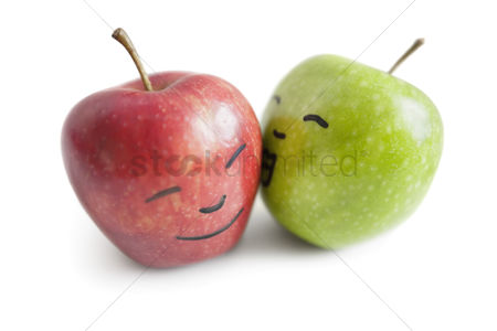 Conceptual : Granny smith apple kissing red apple over white background